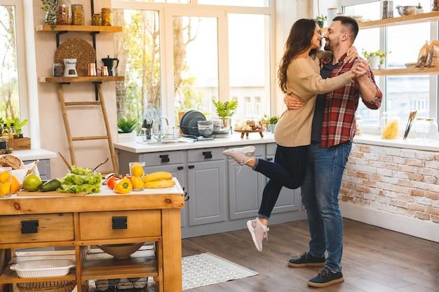 Tańczę W Kuchni. Młoda Romantyczna Para świętuje Zaręczynową Kopii Przestrzeń. śliczna Potomstwo Para Tanczy W Domu. Premium Zdjęcia