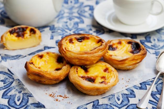 Tarta Jajeczna, Tradycyjny Portugalski Deser, Pastel De Nata Na Pergaminie. Premium Zdjęcia