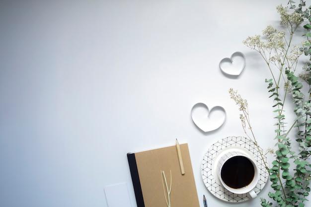 Tasiemkowi serca, notatnik i kawa na białym tle, walentynka dzień. Premium Zdjęcia