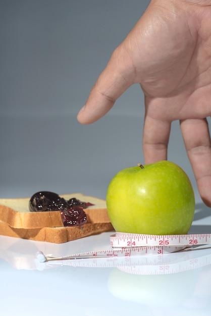 Taśma miernicza owinięta wokół zielonego jabłka Premium Zdjęcia