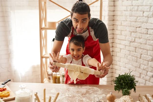 Tata i daighter apingują z ciastem w kuchni. Premium Zdjęcia