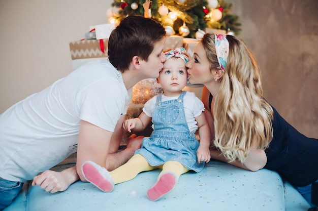 Tata I Mama Całują Małą Córeczkę Z Boku, Pozując W Wystroju Do świątecznego Pokoju. Premium Zdjęcia