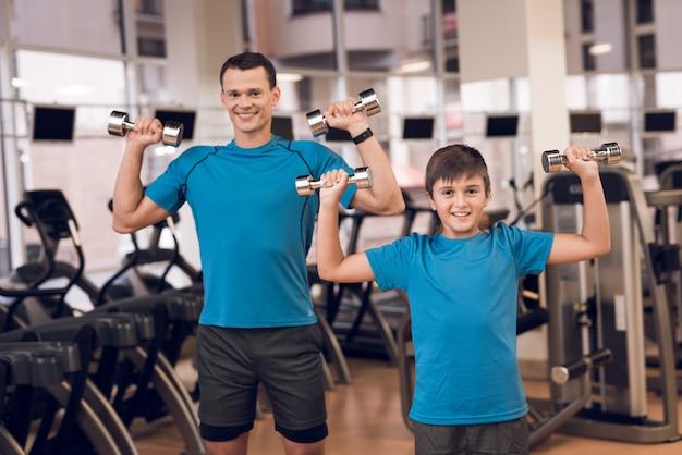 Tata i syn na siłowni robi ćwiczenia z hantlami. Premium Zdjęcia