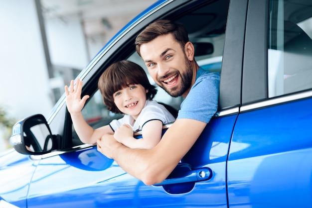 Tata i syn wyglądają przez okno samochodu i uśmiechają się. Premium Zdjęcia