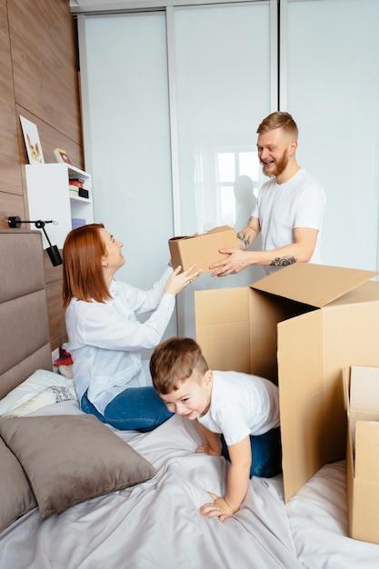 Tata, Mama I Synek Bawią Się W Sypialni Papierowymi Pudełkami Darmowe Zdjęcia