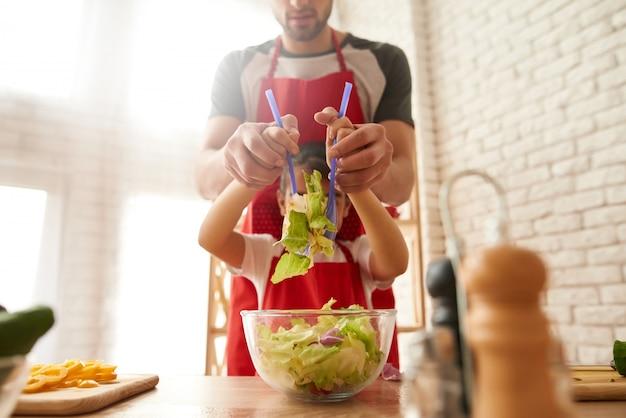 Tata z córką gotuje sałatki na kuchni. Premium Zdjęcia