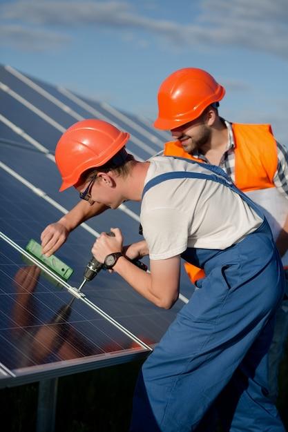 Technicy Instalujący Panele Fotowoltaiczne W Elektrowni Słonecznej. Premium Zdjęcia