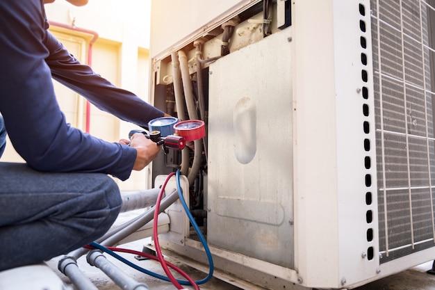 Technik sprawdza klimatyzator, mierzy urządzenia do napełniania klimatyzatorów. Premium Zdjęcia