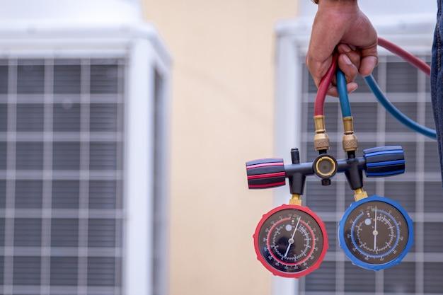 Technik sprawdza klimatyzator, mierzy urządzenia napełniające klimatyzatory. Premium Zdjęcia