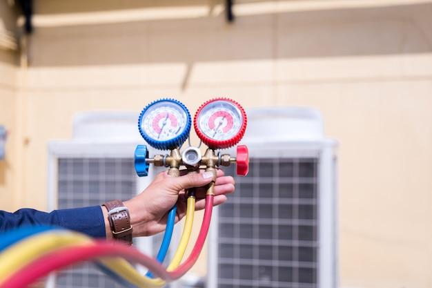 Technik sprawdza klimatyzator, sprzęt pomiarowy do napełniania klimatyzatorów. Premium Zdjęcia