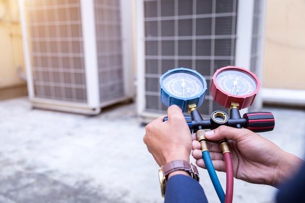 Technik sprawdza urządzenia pomiarowe klimatyzatora do napełniania klimatyzatorów. Premium Zdjęcia
