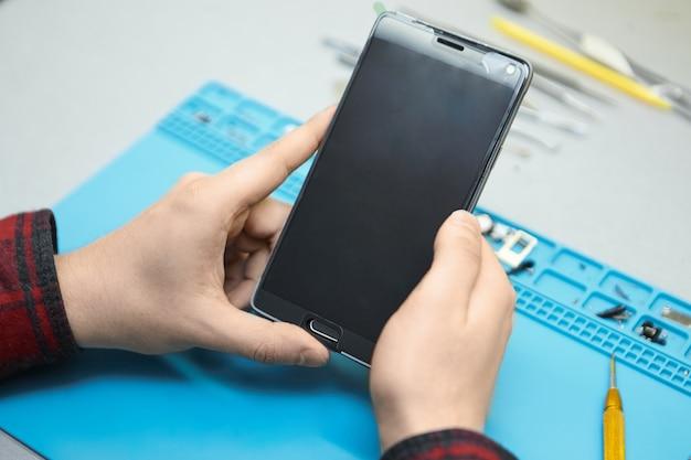 Technik Trzymający Smartfon, Zamierzający Usunąć Pęcherzyki Powietrza Ze Szkła Hartowanego Przymocowanego Do Gadżetu Darmowe Zdjęcia