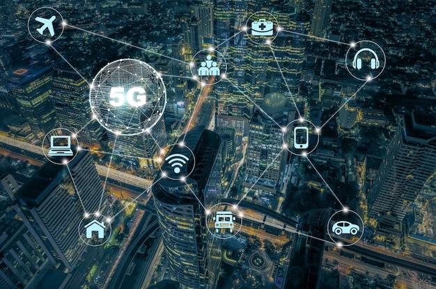 Technologia 5g z różnymi ikonami internetowymi rzeczy ponad widok z góry na nowoczesny budynek z korkiem Premium Zdjęcia