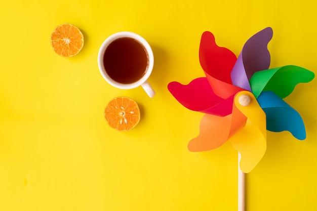 Tęczowy Wiatraczek Na żółto Z Gorącym Napojem I Plasterkami Pomarańczowych Owoców Płasko Leżał Premium Zdjęcia