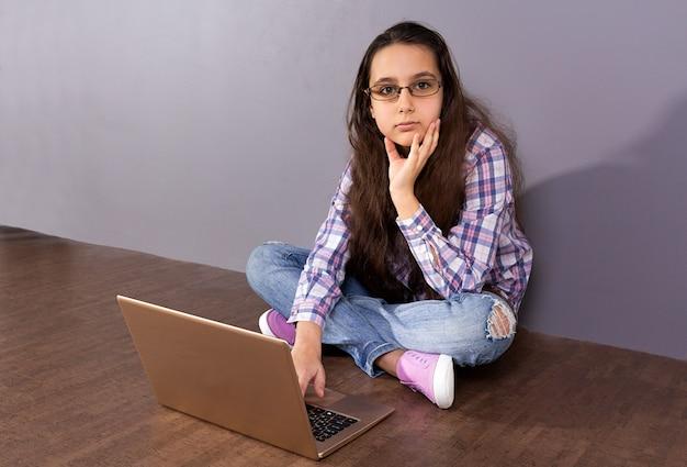Teen Dziewczyna Siedzi Na Podłodze Przed Laptopem. Premium Zdjęcia