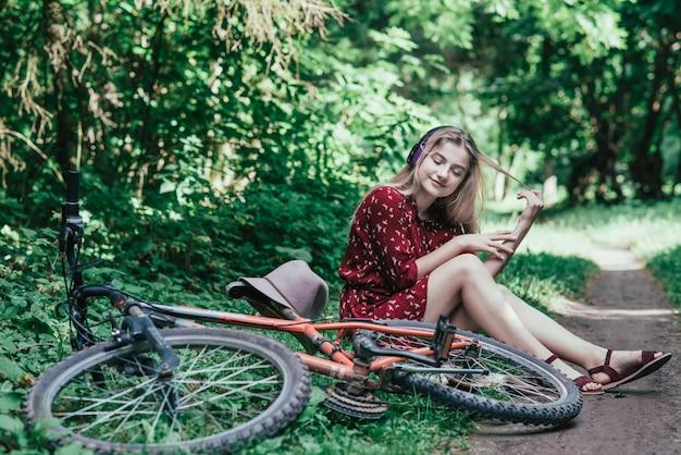 Teen Girl Słuchania Muzyki Z Telefonu Inteligentnego Posiedzenia Z Rowerem W Parku Premium Zdjęcia