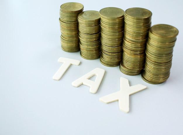 Tekst drewna podatku na złotych monet tła, koncepcji biznesowych i finansów Premium Zdjęcia