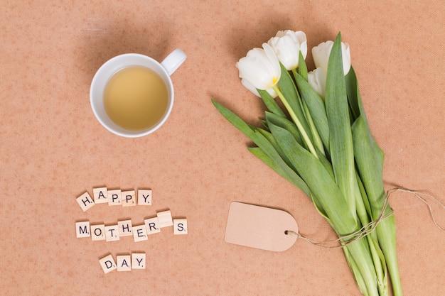 Tekst na dzień matki happy; herbata cytrynowa z białych kwiatów tulipanów na brązowym tle Darmowe Zdjęcia