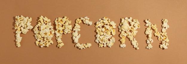 Tekst Popcorn Na Brązowej Przestrzeni, Widok Z Góry. Jedzenie Do Kina Premium Zdjęcia