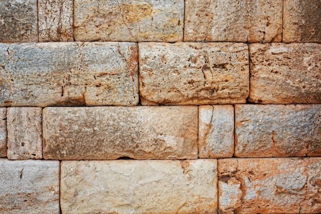 Tekstura kamiennego muru z dużych bloków, elementy budowli starożytnej starożytności. Premium Zdjęcia