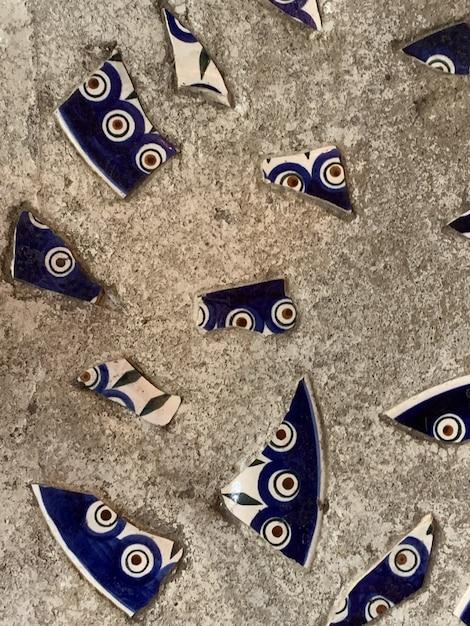 Tekstura ściany, Podłoga Jest Szara Z Kawałkami Połamanej Niebieskiej Porcelany Z Wzorem. Premium Zdjęcia