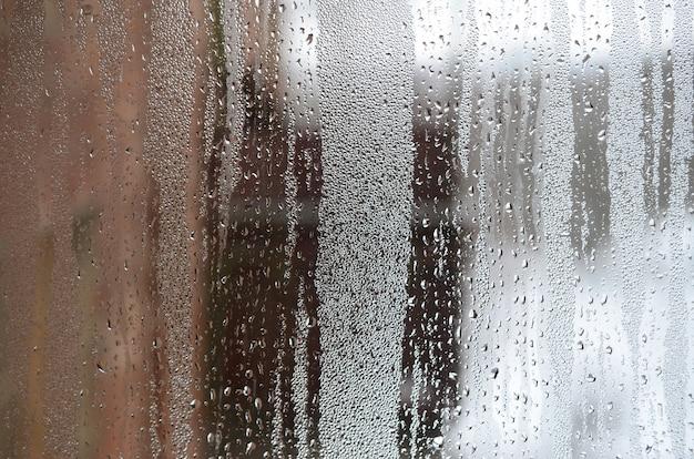 Tekstura zamglonego szkła z dużą ilością kropel i przepływów kondensacyjnych. Premium Zdjęcia