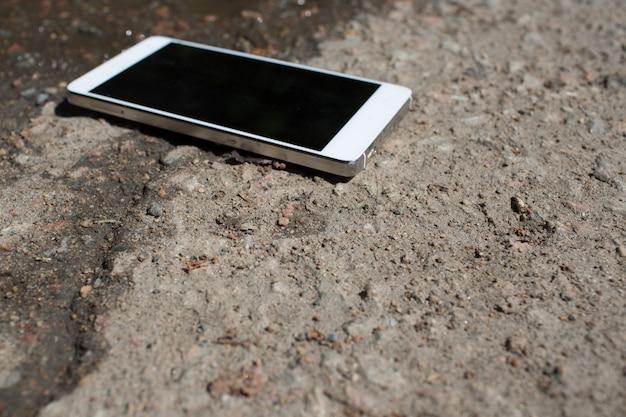 Telefon Komórkowy Leżący Na Asfalcie Chodnika Premium Zdjęcia