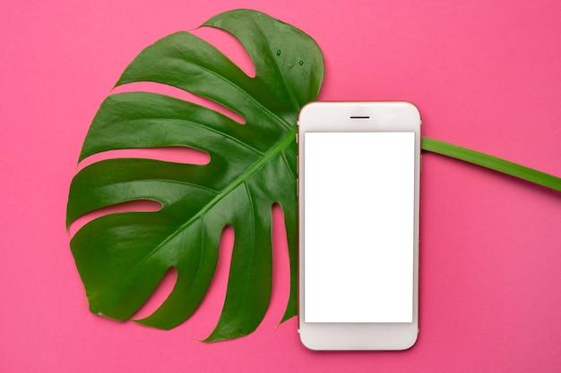 Telefon Komórkowy Z Pustym Ekranem I Tropikalnymi Liśćmi Monstera Na Neonowym Różowym Tle. Kopia Przestrzeń, Płaski Widok Z Góry Premium Zdjęcia