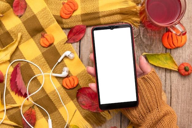 Telefon W Dłoni Dziewczyny Na Tle Opadłych Jesienią Liści I Szalik. Premium Zdjęcia