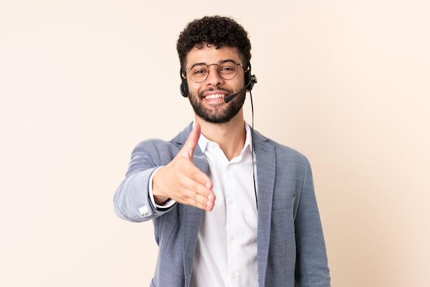 Telemarketer Marokański Mężczyzna Pracujący Z Zestawem Słuchawkowym Odizolowanym Na Beżowej ścianie, ściskający Ręce Za Zawarcie Dobrej Transakcji Premium Zdjęcia