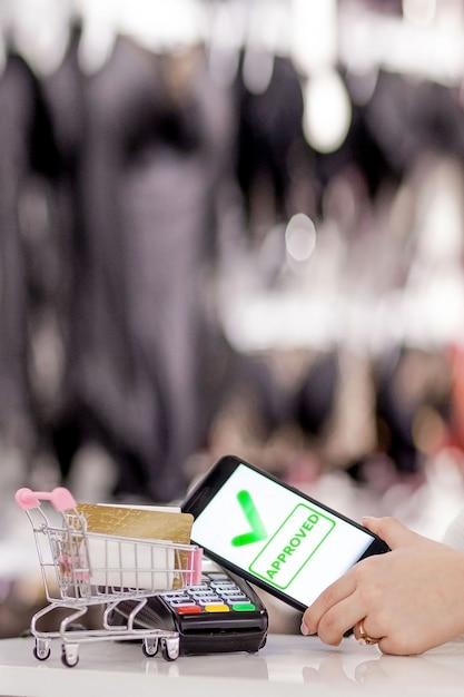Terminal Pos, Maszyna Płatnicza Z Telefonu Komórkowego Na Tle Sklepu. Płatność Zbliżeniowa Z Technologią Nfc Premium Zdjęcia