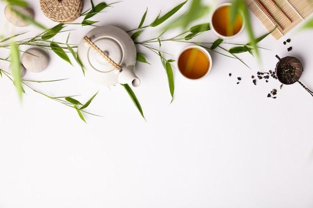 Tło azjatyckie jedzenie z zielonej herbaty, filiżanki i czajnik z gałęzi bambusa Premium Zdjęcia