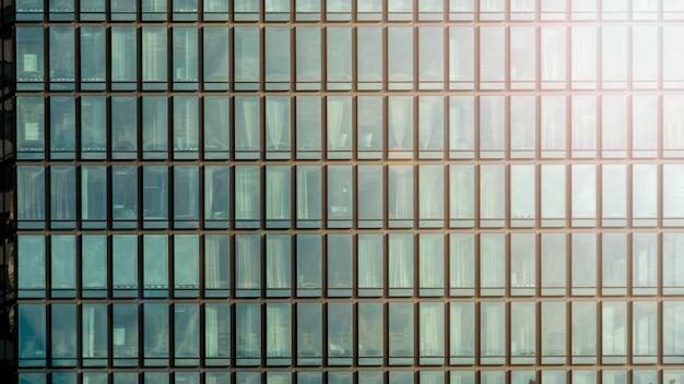 Tło nowożytnego budynku architektury ściany błękitny szklany glazing w deseniowym sześcianie i kwadracie z oświetleniowym światłem słonecznym Premium Zdjęcia