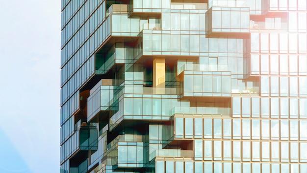Tło nowożytnego budynku architektury ściany błękitny szklany glazurowanie w deseniowym sześcianie i kwadratowym nasunięciu z oświetleniowym światłem słonecznym Premium Zdjęcia