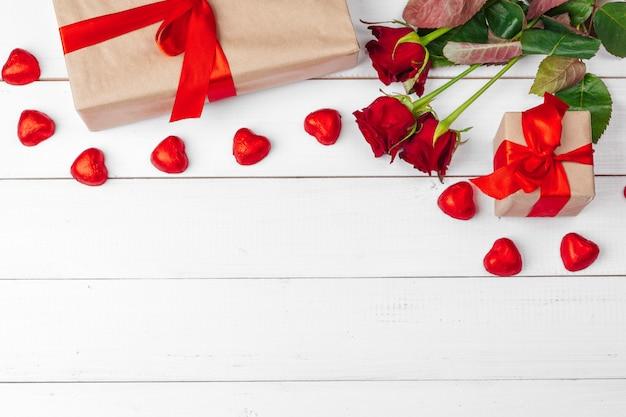 Tło st. walentynki. czerwone róże i pudełko na drewnianym stole Premium Zdjęcia