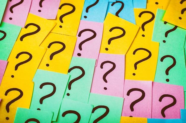 Tło znaków zapytania. kolorowe papierowe notatki ze znakami zapytania. obraz koncepcji. widok z góry zbliżenie stonowanych Premium Zdjęcia