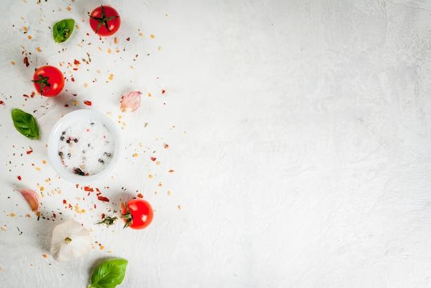 Tło żywności Składniki, Warzywa I Przyprawy Do Gotowania Lunchu, Lunchu. świeże Liście Bazylii, Pomidory, Czosnek, Cebula, Sól, Pieprz. Na Białym Kamiennym Stole. Widok Z Góry Lato Premium Zdjęcia