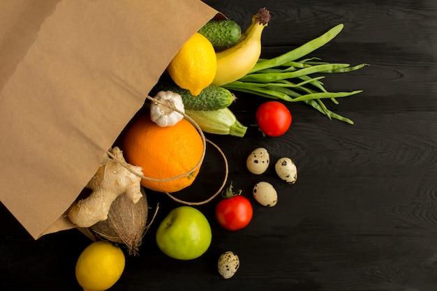 Torba Papierowa Z Warzywami I Owocami Na Czarnej Drewnianej Powierzchni. Koncepcja żywności Worek. Widok Z Góry Miejsce Na Kopię. Premium Zdjęcia