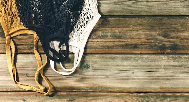Torby Na Zakupy Wielokrotnego Użytku Na Drewnianym Tle. Koncepcja Zero Odpadów. Premium Zdjęcia