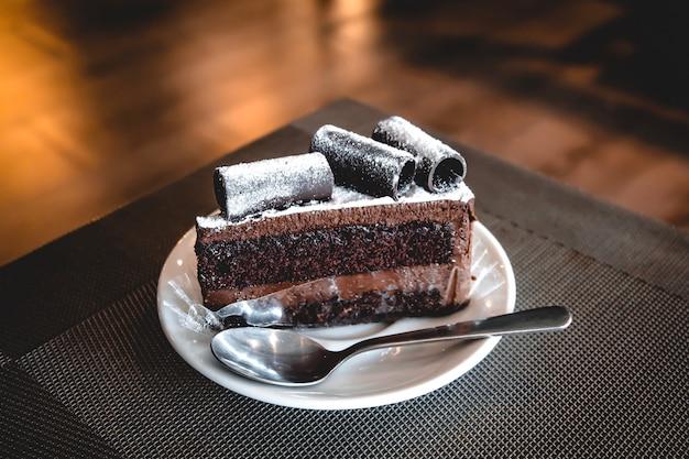 Tort brownie wite rolka czekolady na wierzchu na białej płytce ceramicznej mają łyżeczkę. Premium Zdjęcia