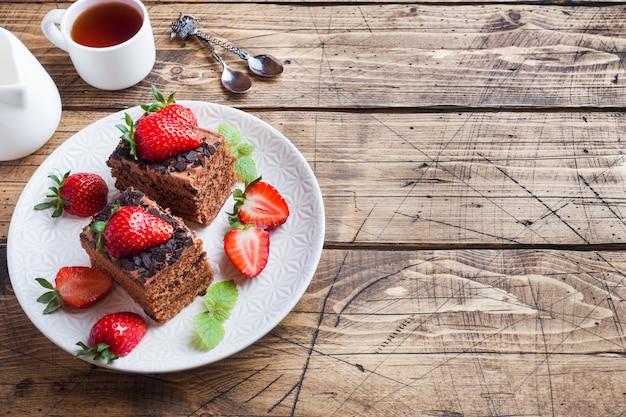 Tort Czekoladowo-truflowy Z Truskawkami I Miętą. Drewniany Stół. Skopiuj Miejsce Premium Zdjęcia