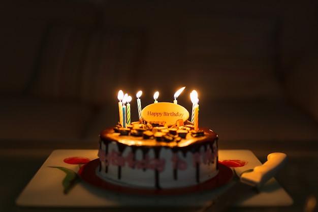 Tort Urodzinowy Na Czarnym Stole Z Zapalonymi Kolorowymi świeczkami. Premium Zdjęcia