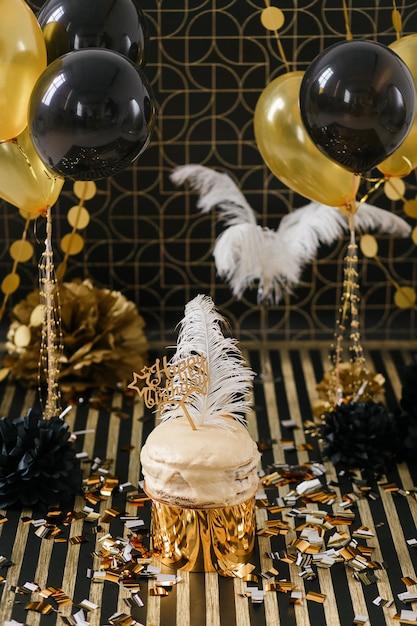 Tort urodzinowy z złote i czarne dekoracje różnych balonów. Darmowe Zdjęcia
