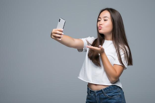 Towarzyska Piękna Azjatykcia Dziewczyna Bierze Selfie Lub Mówi Na Rozmowie Wideo Używać Telefon Komórkowego Nad Szarym Tłem Darmowe Zdjęcia