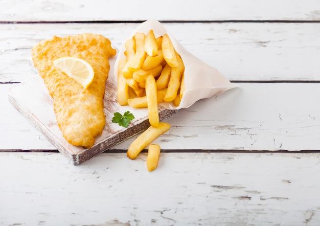 Tradycyjna Brytyjska Ryba Z Frytkami Z Sosem Tatarskim Na Desce Do Krojenia Na Białym Drewnianym Stole. Premium Zdjęcia