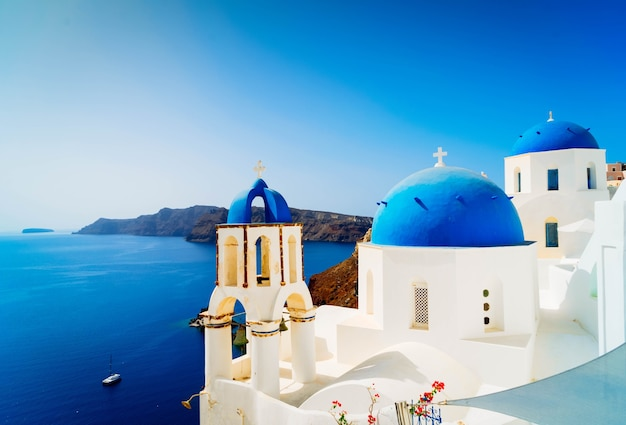 Tradycyjna Grecka Wioska Oia Na Santorini, Z Niebieskimi Kopułami Na Tle Morza I Kaldery, Grecja, Stonowanych Premium Zdjęcia