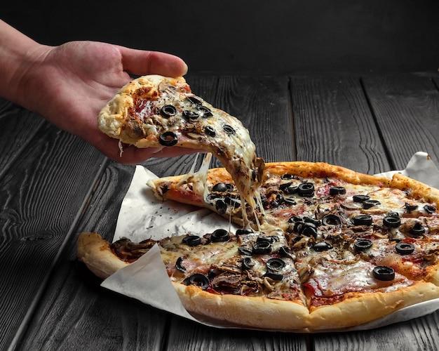 Tradycyjna Włoska Pizza Na Ciemno Czarnej Desce, Kawałek Pizzy W Ręku, Premium Zdjęcia