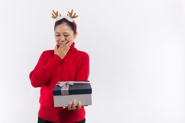 Tradycyjne ferie zimowe. skarpeta świąteczna koncepcja. sprawdź zawartość skarpet świątecznych. kobieta w santa hat trzymać prezent na boże narodzenie Premium Zdjęcia