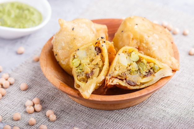 Tradycyjne indyjskie jedzenie samosa w drewnianej tablicy z miętowym chutney Premium Zdjęcia