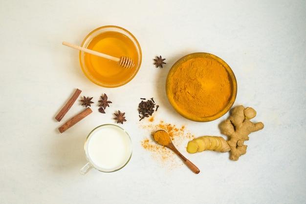 Tradycyjne Indyjskie Złote Mleko Z Kurkumą, Imbirem, Przyprawami, Miodem. Premium Zdjęcia